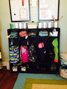 """Super cool $5 find from a school that was renovating. Add black chalkboard paint and Voila! (2 dry erase boards above to keep important notes for each kiddo. Old formula cans for craft/school supplies. Basket in the middle for """"Hair Stuff"""" to fix hair up and spray it every morning (lice ain't standing a chance in this house)"""